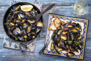 Traditional barbecue Italian blue mussel in white wine as top view on a plate