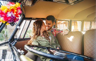 Woman and man enjoy in classic van.
