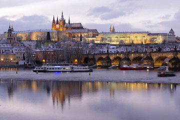 Evening colorful snowy Christmas Prague Lesser Town with gothic Castle and Charles Bridge, Czech republic