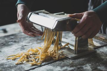 Female preparing Italian traditional tagliatelle pasta,selective focus