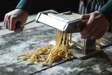 Female preparing Italian traditional tagliatelle with machine,blurred motion and selective focus