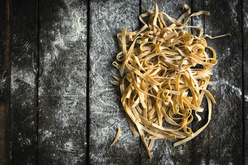 Prepared Italian traditional tagliatelle splashed on the wooden table,blank space