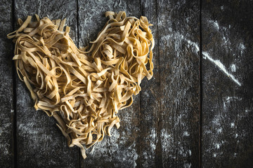 Prepared Italian traditional tagliatelle in heart shape on wooden background with blank space,Valentine day concept