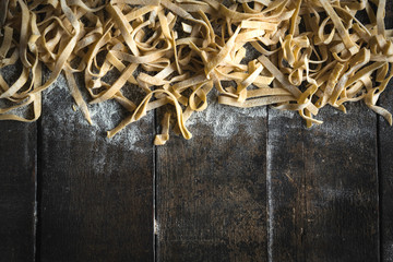 Prepared Italian traditional tagliatelle splashed on wooden background with blank space