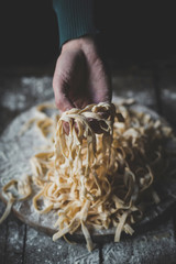 Female holding Italian traditional tagliatelle in her hands,selective focus