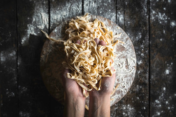 Italian traditional tagliatelle in female hands,selective focus