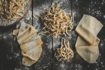 Italian traditional tagliatelle splashed on the wooden table,high angle