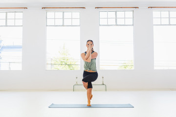Caucasian woman performing yoga twisting arms and legs