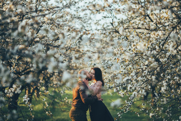 Caucasian couple kissing near blooming trees