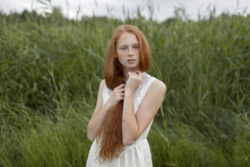 Portrait of serious Caucasian girl with freckles standing in field