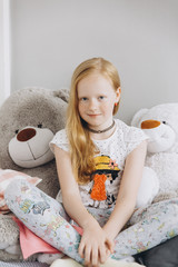 Smiling Middle Eastern girl sitting with large teddy bears