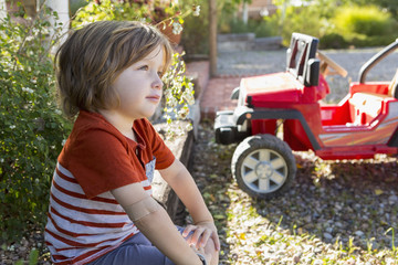 Pensive Caucasian boy sitting near toy car