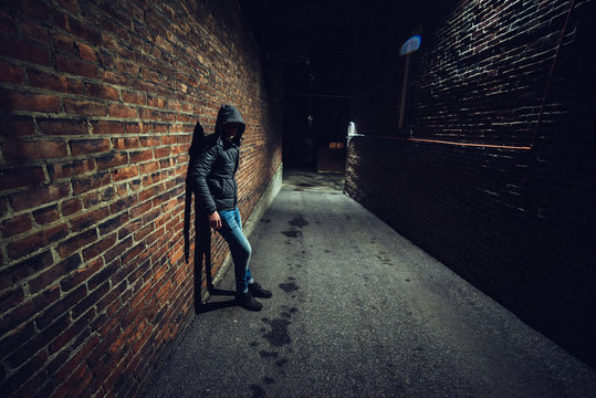 Suspicious man in dark alley waiting for something