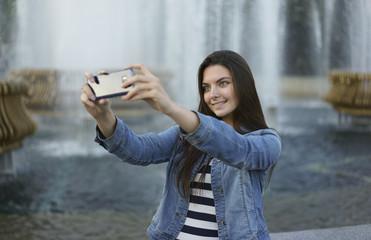Caucasian woman posing for cell phone selfie near fountain