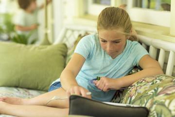 Caucasian girl sitting on sofa watching digital tablet