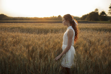 Pensive Caucasian girl standing in field of wheat