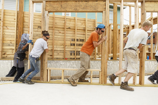 Volunteers pushing framed wall at construction site
