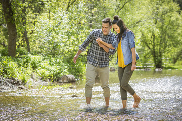 Couple holding hands wading in river