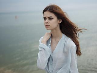 Pensive Caucasian woman standing near ocean