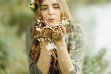 Middle Eastern woman blowing dandelion seeds