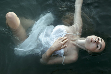 Caucasian woman wearing a dress floating in water