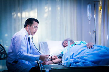 Asian young doctor checking blood pressure of patient elderly