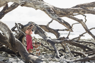 Caucasian mother and daughter climbing on driftwood at beach