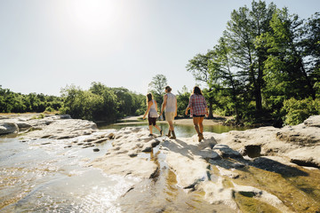 Friends walking on rocks near river