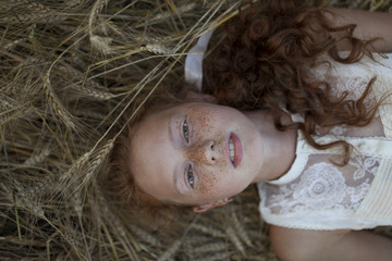 Caucasian girl laying in wheat