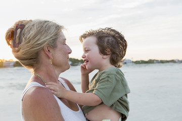 Mother holding boy at beach