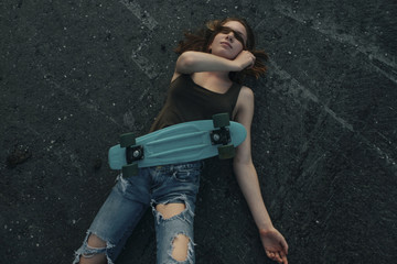 Caucasian teenage girl with skateboard laying on pavement covering eyes