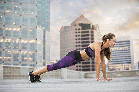 Caucasian woman doing push-ups on urban rooftop