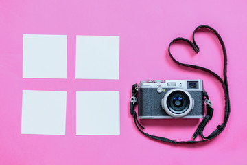 Vintage photo camera on Valentine's Day pink background with composition of blank photo frames, empty notes and hearts, top view. flat lay