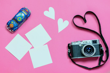 Vintage photo camera on Valentine's Day pink background with composition of volkswagen beetle hippie style, blank photo frames, empty notes and hearts, top view. flat lay