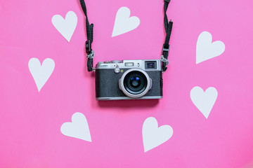 Vintage photo camera on Valentine's Day pink background with composition of blank photo frames and hearts, top view. flat lay