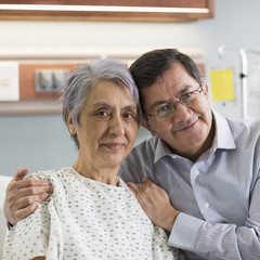 Portrait of smiling Hispanic man with woman in hospital bed