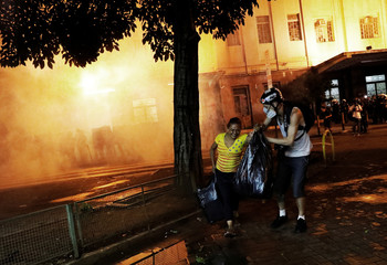 Photographer Felipe (R) helps a citizen after students clash with riot police during a protest against fare hikes for city buses in Sao Paulo