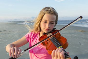 Caucasian girl playing violin on windy beach