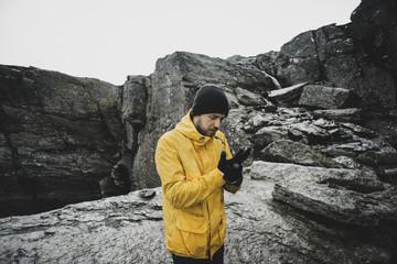 Caucasian man adjusting gloves on mountain