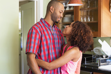 Mixed race couple hugging in kitchen