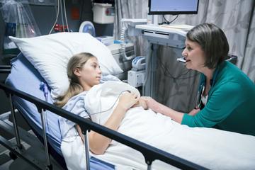Caucasian doctor comforting patient in hospital bed