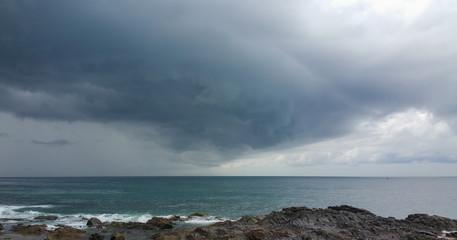 Black rain clouds over the sea