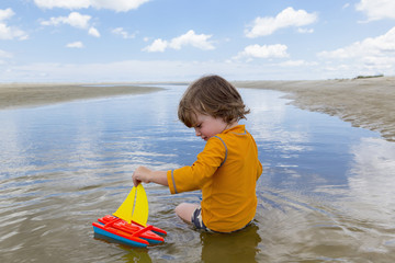Caucasian boy sitting in water playing with toy sailboat