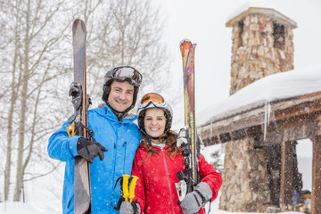 Portrait of smiling Caucasian couple carrying skis