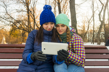 Caucasian women sitting on park bench in the winter holding digital tablet