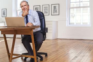Portrait of smiling Caucasian businessman using laptop