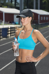 Cute and fit young teen Caucasian girl working out on outdoor track looks off frame with a water bottle