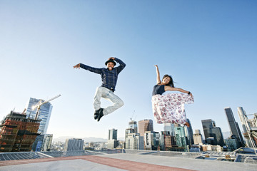 Couple dancing and jumping on urban rooftop