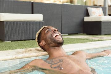 Smiling Black man relaxing in swimming pool