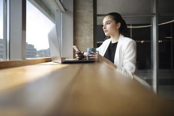 Business woman drinking coffee and texting on cell phone